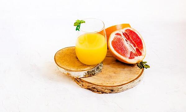 a glass of juice next to a grapefruit